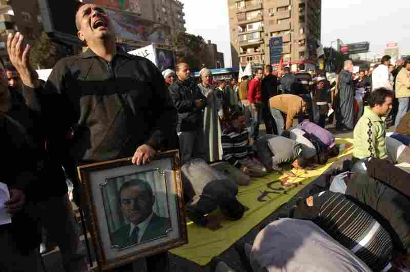 A Coptic Christian supporter of President Hosni Mubarak holds the leader's picture while praying with Muslim fellows in Cairo's  Muhandisin district on Feb. 2.