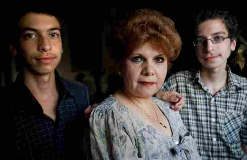 Camillia Lutfi, center, with her 16-year-old twin sons Mario Ramses, left, and Andrew Ramses, right, at their home in Alexandria, Egypt, Nov. 11, 2010. Camillia and her sons have been fighting to keep the two boys Christians after their father converted to Islam.