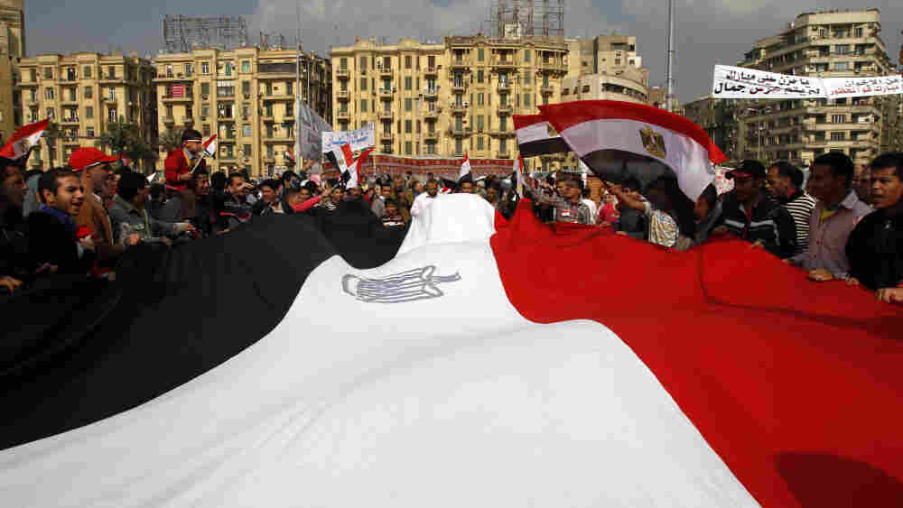 Egyptian anti-government demonstrators held a huge national flag as they gathered in Cairo's Tahrir Square on Wednesday (Feb. 9, 2011).