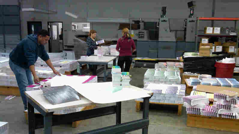 Workers at the Pantone factory in Carlstadt, N.J., sort through freshly printed color sheets.