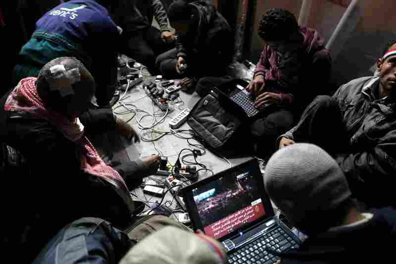 Egyptian anti-government bloggers work from their laptops in Tahrir Square.