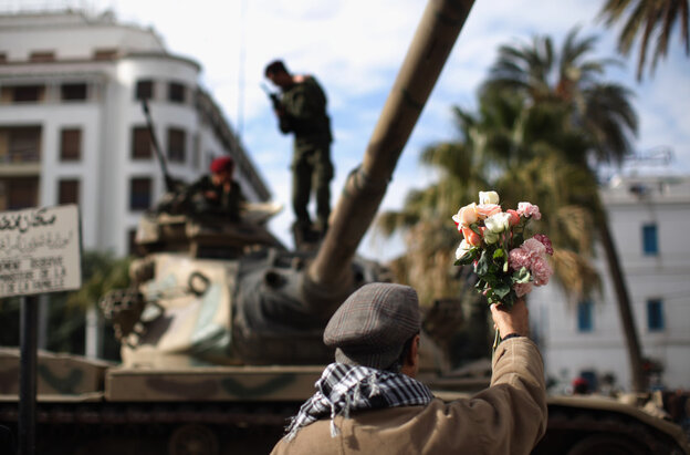 A demonstartor offers flowers to soldiers on their tank as an un-easy peace hangs over Tunisia on January 21, 2011.