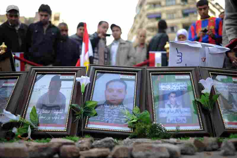 Egyptians visit a makeshift memorial for anti-government protesters killed during clashes with police and pro-government forces at Tahrir Square.