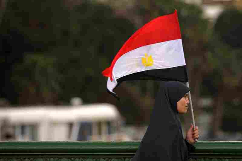 A woman holds the national flag as she walks across a bridge leading to Tahrir Square.