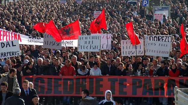 Opposition supporters carrying banners and Albanian national flags participate in an anti-government protest in the town of Vlora, Albania, on Feb. 4.