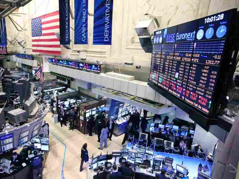 Traders work at the New York Stock Exchange on Thursday as a merger with the German exchange, Deutsche Boerse, moved forward.