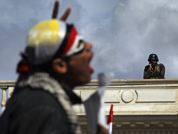 As an anti-government protester chanted today in Cairo, an Egyptian Army soldier watched from the roof of parliament.