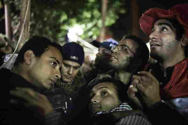 Egyptian anti-government demonstrators in Tahrir Square listen to a speech by  President Hosni Mubarak.