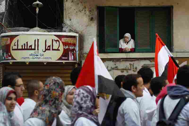 A woman looks out her window as medical school students and professors march by in Cairo.