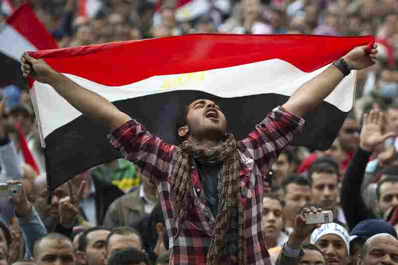 An anti-goverment protester holds the Egyptian national flag as he shouts slogans against president Hosni Mubarak in Tahrir Square on Thursday, Feb. 10, the 17th day of protests.