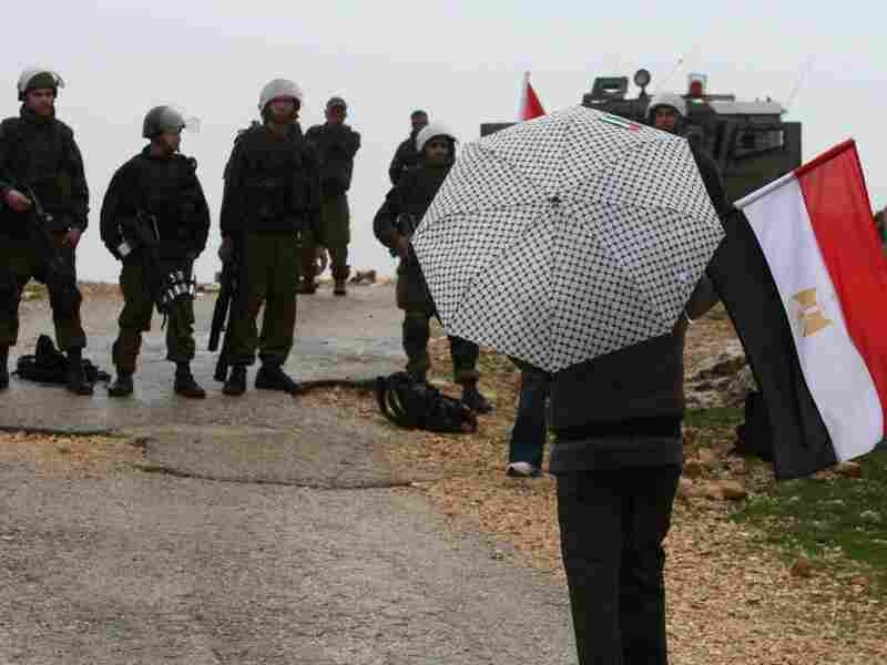 A Palestinian demonstrator holds an Egyptian flag and a Fatah party umbrella while facing Israeli forces during a protest against Israel's separation barrier in the West Bank.