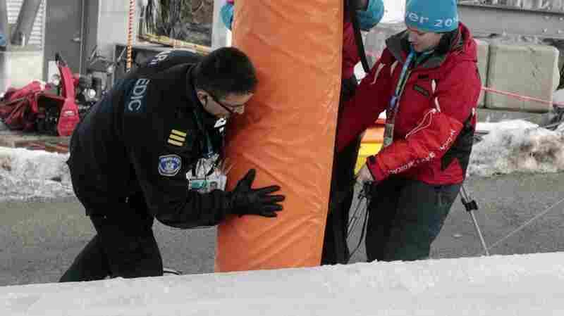 Paramedics and track staff add padding to the poles that slider Nodar Kumaritashvili crashed into ahead of the 2010 Winter Games.