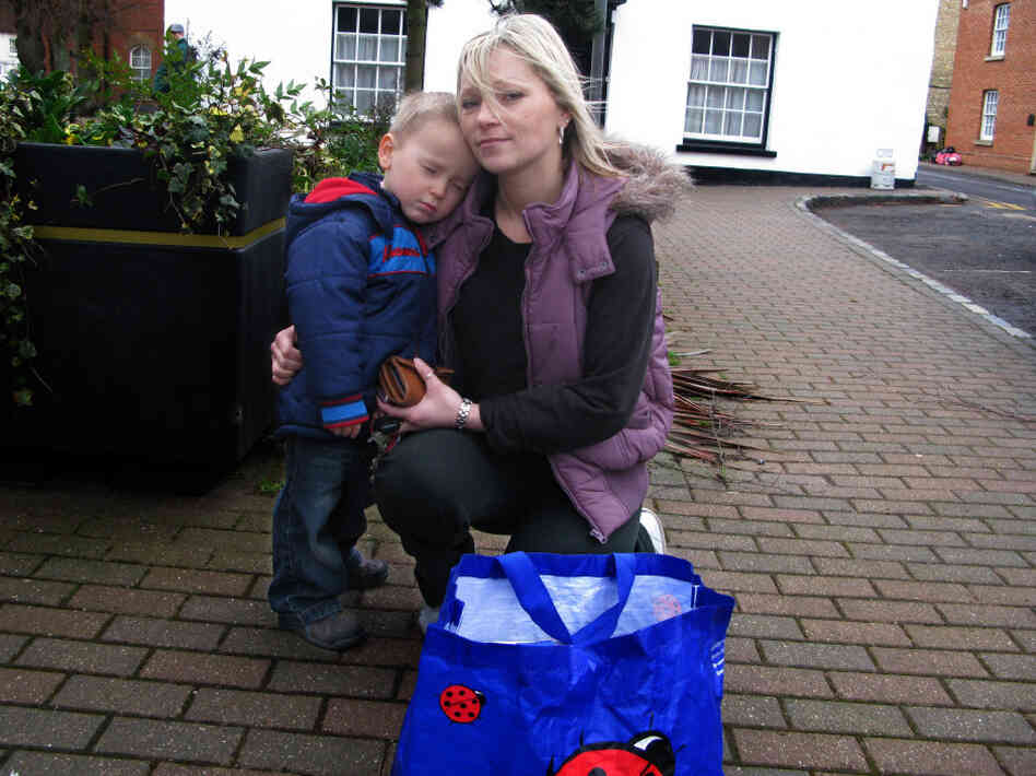 Sarah Richardson and her son, Harry, return a bag of books to the Stony Stratford Library. She took out the books as part of a protest against the possible closure of the library.