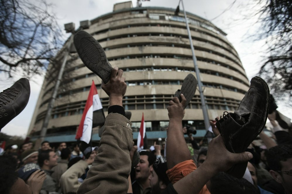 In a gesture of disrespect Friday, anti-government protesters raise their shoes in front of the Egyptian national TV building, which is currently secured by the Egyptian army.