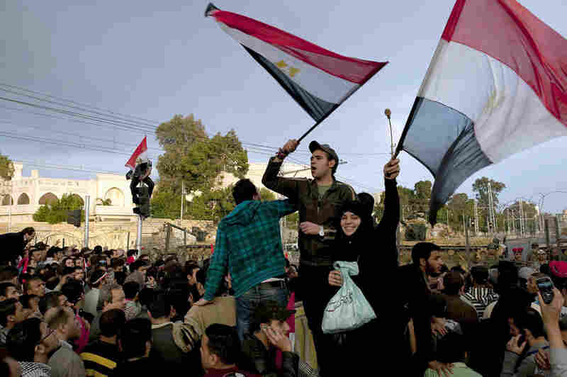 Protesters wave flags outside the Presidential Palace on Friday. Cairo's streets exploded in celebration when Mubarak stepped down after three decades of autocratic rule.