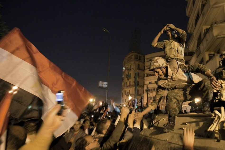 Egyptian soldiers celebrate with anti-government protesters. Vice President Omar Suleiman announced the military will take control over affairs of state.  (AFP/Getty Images)
