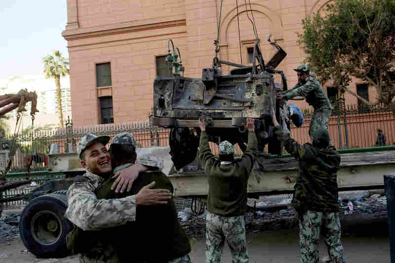 Soldiers hug as others remove the wreckage of a car burned during the anti-government protests in Cairo.