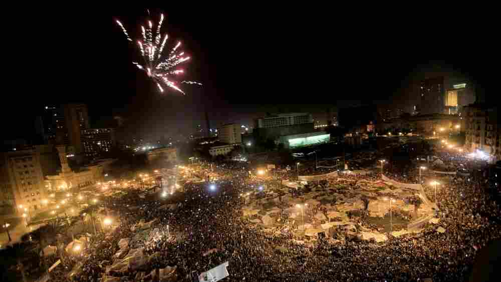 Egyptian anti-government protesters celebrate under fireworks at Cairo's Tahrir Square after president Hosni Mubarak stepped down.