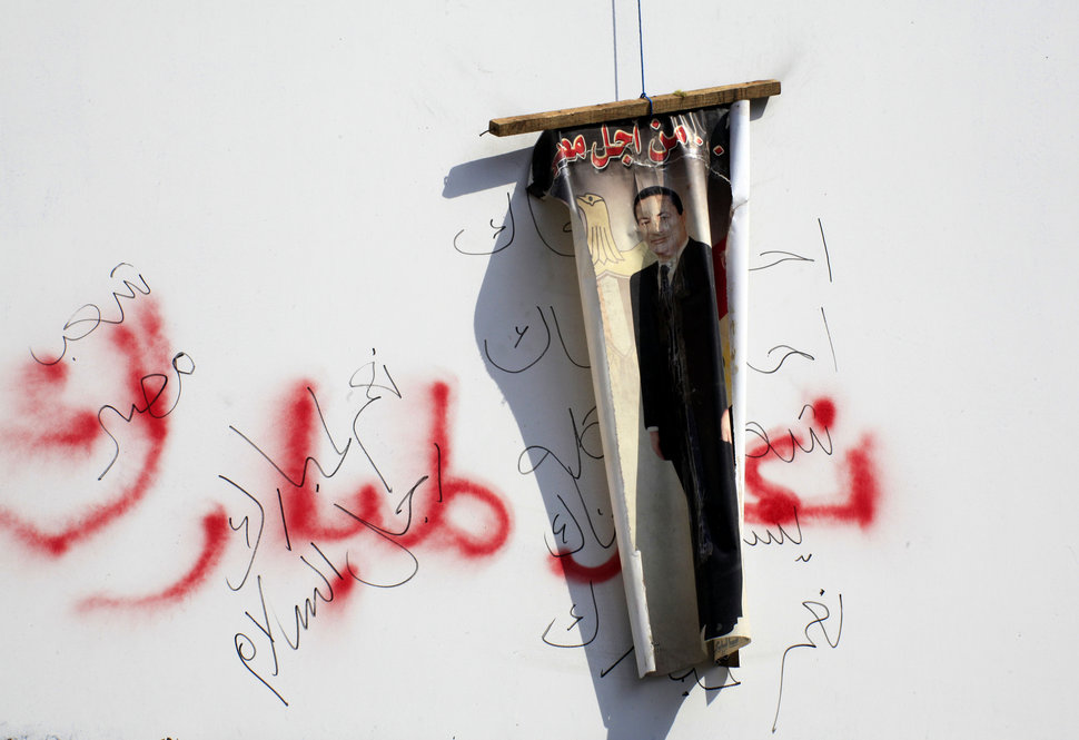 An anti-Mubarak poster hangs over graffiti endorsing the president. Clashes between anti-government protesters and Mubarak supporters have thrown Cairo into violence.