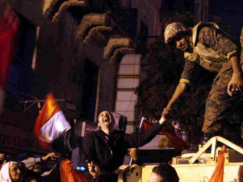 An Egyptian anti-government protester laughs as he shakes the hand of a soldier during celebrations at Cairo's Tahrir Square on Feb 11 after president Hosni Mubarak stepped down. Flag-waving Egyptians danced, sang and cheered as they bid farewell to Hosni Mubarak's 30-year regime, but triumph was tempered with apprehension as they looked ahead to military rule.