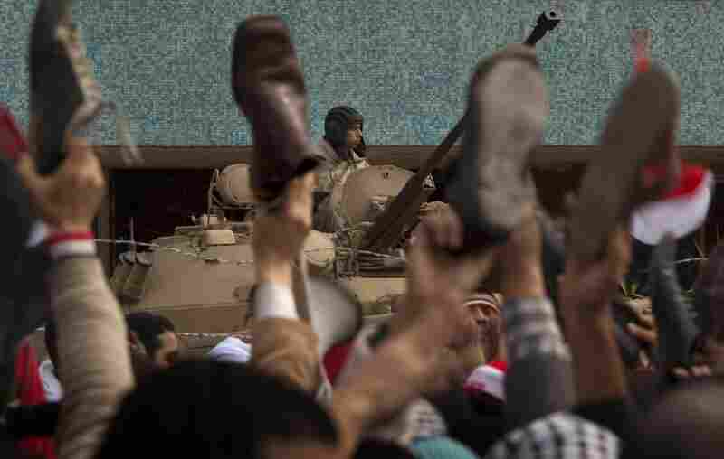 An army soldier sits on an armored vehicle as anti-government protesters hold their shoes in the air during a protest in front of the state television building Friday in downtown Cairo.