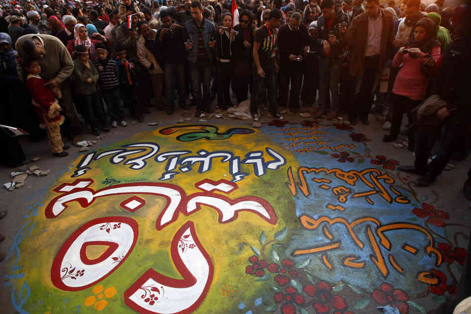 "Egyptians gather around graffiti that reads, ""January 25, Egypt's greatest and noblest day, Martyrs Square"" in Tahrir Square."