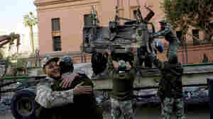 Soldiers hug as others remove the wreckage of a car burned during the uprising at Cairo's Tahrir Square.
