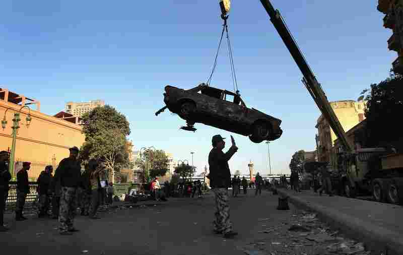 Soldiers remove a car burnt during clashes in Tahrir Square.