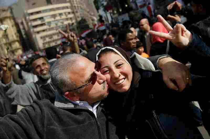 Egyptians embrace while celebrating Mubarak's resignation.
