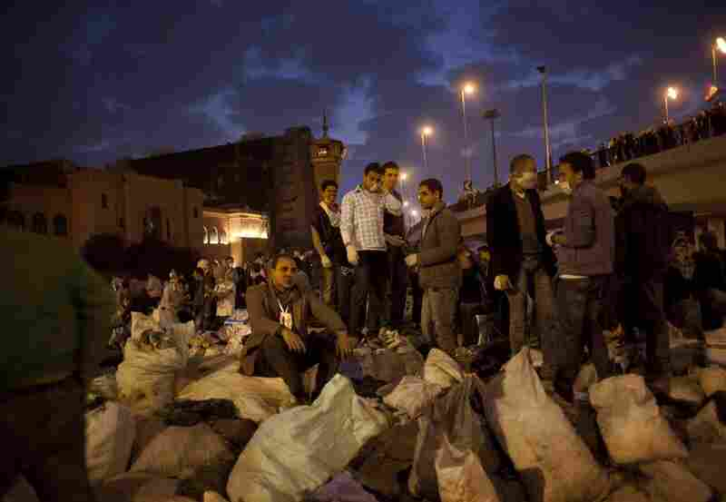 Egyptians stand on top of sacks of garbage collected from the streets of Tahrir Square in Cairo on Saturday.