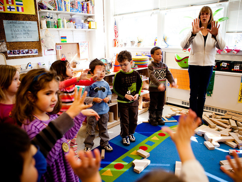 Cathie Morton, a teacher at the Clara Barton  Center for Children, leads the kids in a clapping exercise to signal that it is time to shift gears and start cleaning up. (NPR)