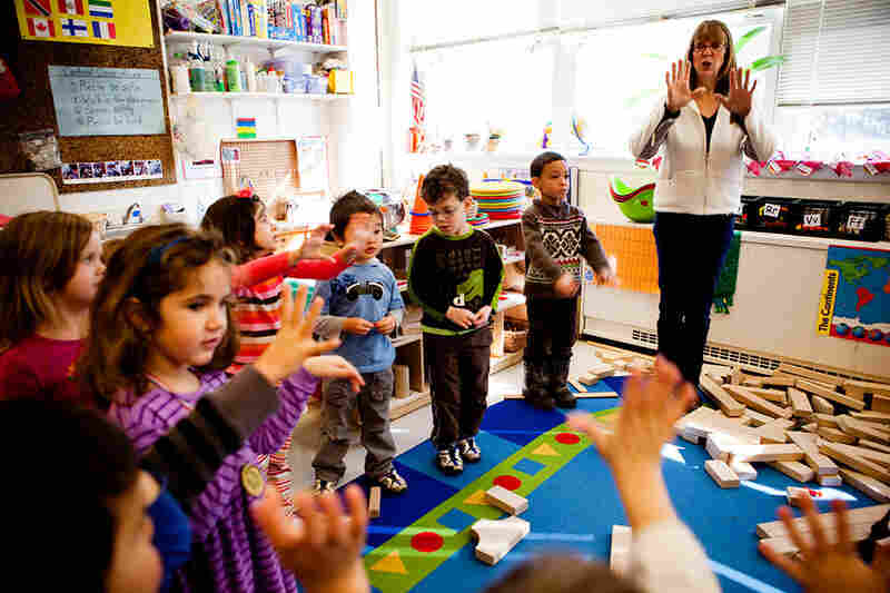 Cathie Morton, a teacher at the Clara Barton  Center for Children, leads the kids in a clapping exercise to signal that it is time to shift gears and start cleaning up.