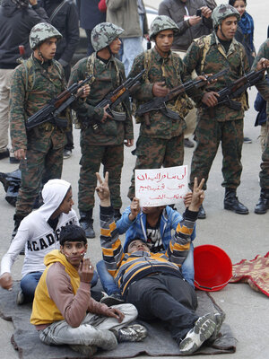 """Egyptian protesters hold a placard reading """"We will not leave the square until we get all our demands,"""" as they sit in front of soldiers in Cairo's Tahrir Square on Sunday."""