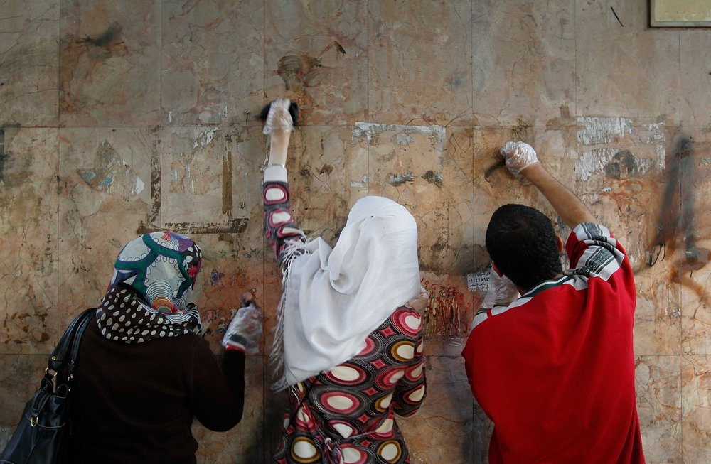 Volunteers scrub paint and graffiti off of a wall in Tahrir Square. Cleaning crews, both paid and unpaid, made quick work of cleanup where thousands of protesters lived and fought for more than two weeks.