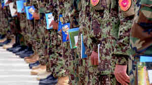 Afghan National Army soldiers line up with their literacy instruction materials  in hand Aug. 7, 2010, at the Capital Division Headquarters.