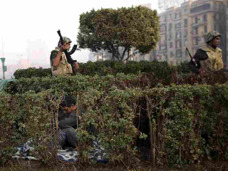 Egyptian soldiers wake up protesters while trying to clear Tahrir Square in Cairo on Monday morning.