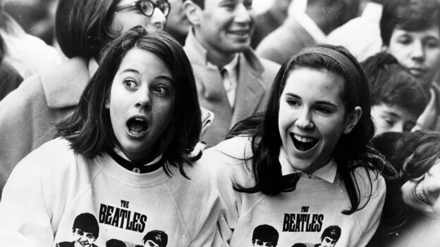 Two Beatles fans welcome the group as they arrive in New York in February 1964.