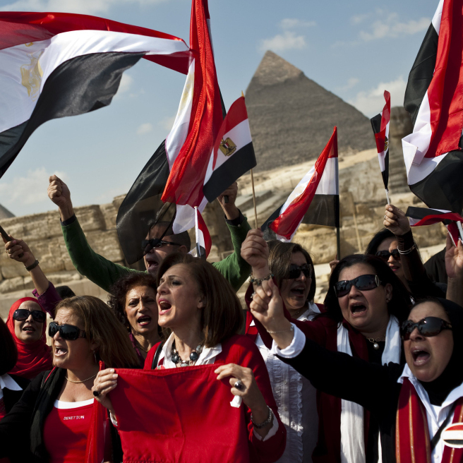 Egyptian tour guides wave their national flag as they call on tourists to return to the country following the fall of Hosni Mubarak's regime, at the Giza pyramids on the outskirts of Cairo.