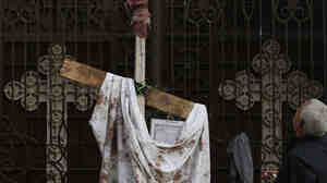 An Egyptian man stands next to a bloodstained piece of cloth used to cover the victims of the New Year's Eve car bomb explosion outside the Coptic Al-Qiddisine church in Alexandra, Egypt. Twenty-one people were killed in the attack against Egypt's Christian community, the largest in the Middle East.