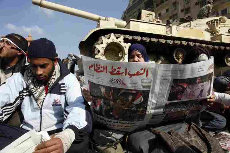 Egyptians read about Friday's events in front a tank.