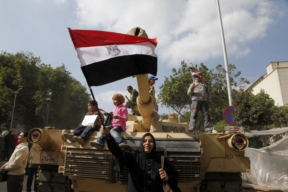 An Egyptian woman waves the national flag in front of a tank.