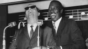 British jazz pianist George Shearing (left) and American singer Joe Williams attend a press reception in London in 1962 before beginning a tour of Britain together.