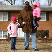 Robert  Adams carries his daughter Layla, 2, and walks with Lucy, 4, in front of their home in District Heights, Md. Adams grew up near the Anacostia Historic District  of Washington, D.C., but couldn't afford to buy a home  there for his family. He now lives in this suburb, a few miles away from his mother and  grandmother, who still live in the house where he grew up.