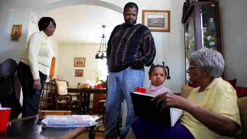 Robert  Adams, with his daughter Lucy,  grandmother Lucy Stith,  90,  right, and mother, Hattie  Adams. They look through old  family photographs at Hattie Adams' house near historic Anacostia.