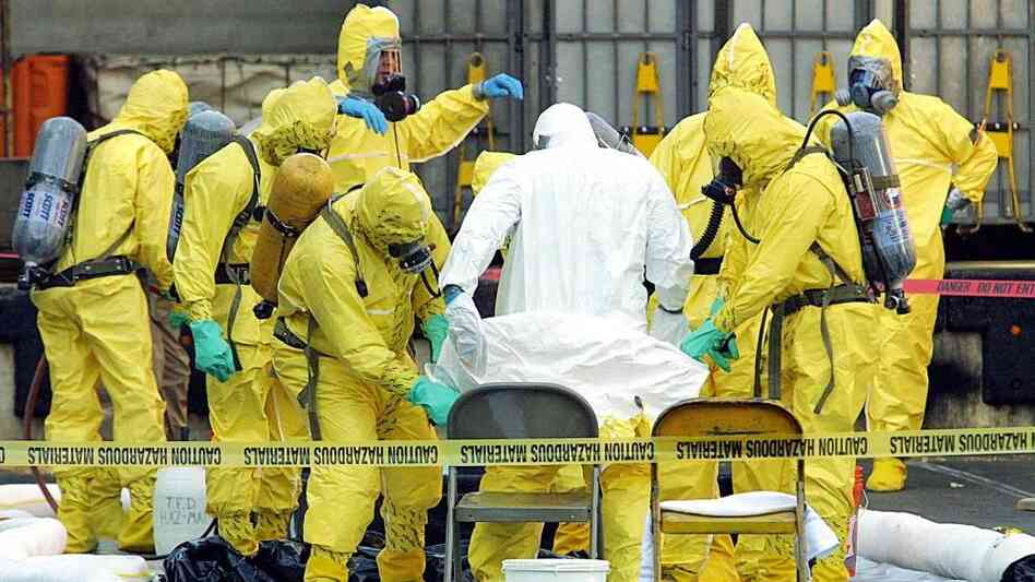 Members of a hazardous materials response team help to remove a