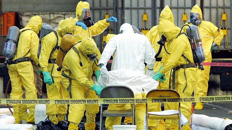 Members of a hazardous materials response team help to remove a hazardous materials suit from an investigator who had emerged from the U.S. Post Office in West Trenton, N.J., on Oct. 25, 2001.  The post office was closed after two letters containing anthrax were traced back to this facility.