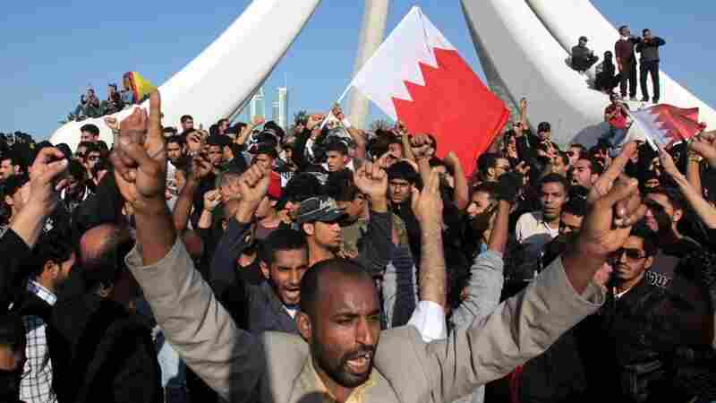 Demonstrators chant and wave Bahraini flags near the Pearl Monument on a  main square in Manama, Bahrain, Tuesday. Thousands of  protesters poured into the square in Bahrain's capital in an Egypt-style  rebellion that sharply escalated pressure on authorities as the Arab  push for change gripped the Gulf for the first time.