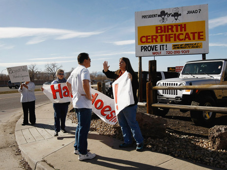 Obama supporter Mary Schaeffer argues with critic Gary Henderson near a birther billboard,  November 2009.