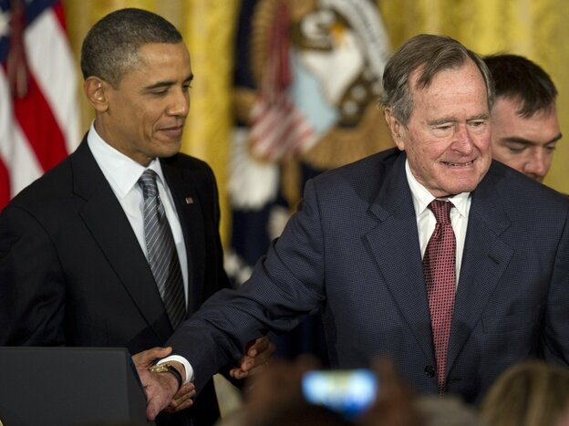 President Obama assists former President George H.W. Bush during todays Medal of Freedom ceremony at the White House.