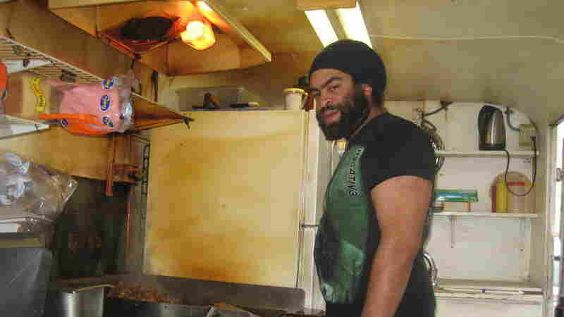 Quentin Gardiner huddles over the grill in a food cart in downtown, Portland. Gardiner is from Binghamton, N.Y., and says he moved to the city for the heavy metal rock scene.